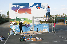 With the noise of elementary school-age kids playing in the background and with an occasional ball or two bouncing near them, California Baptist University art students continued with their task at hand—painting a mural in the school's playground.