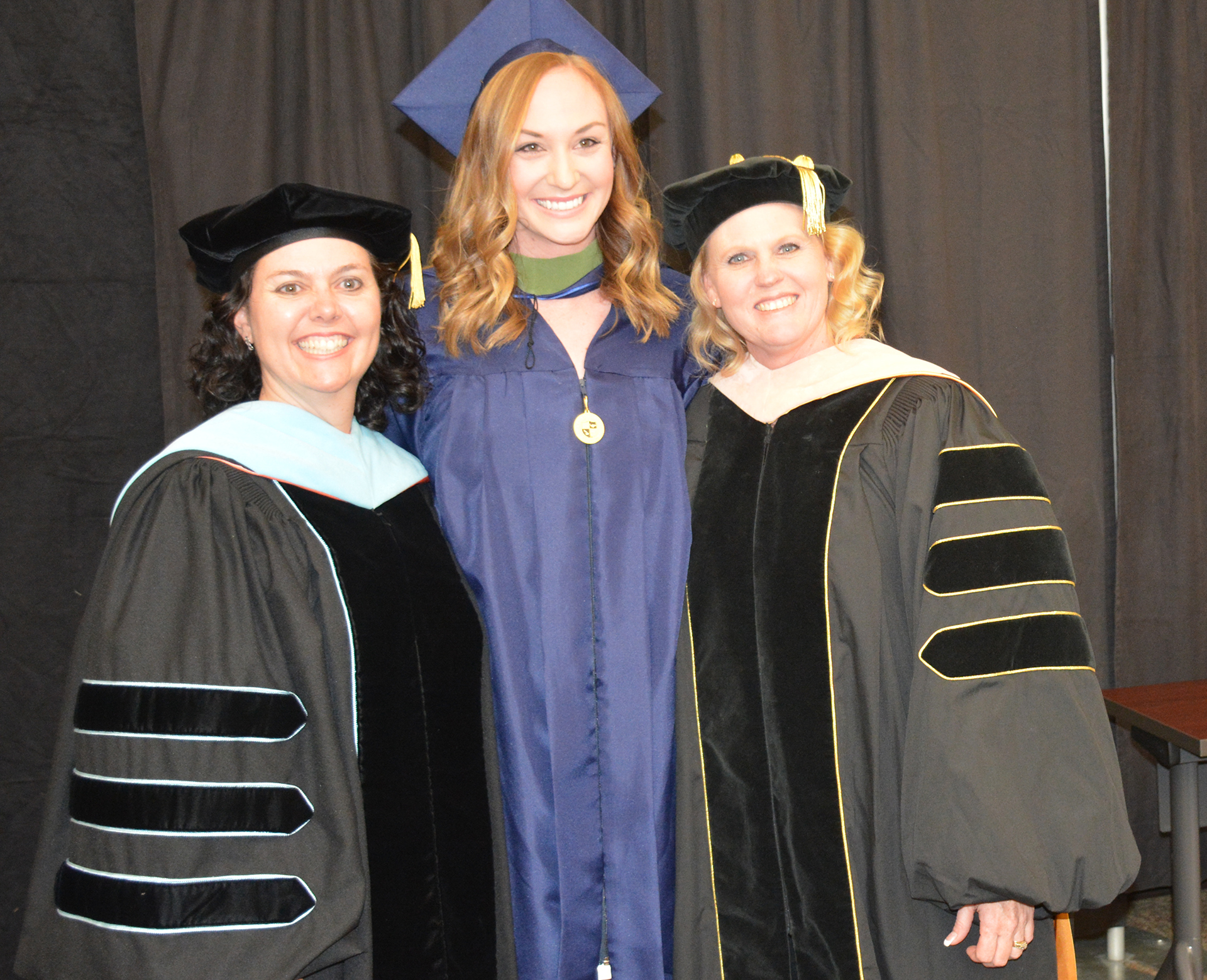 Graduate students participate in hooding ceremonies before commencement