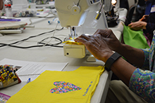 More than 25 sewing machines whirred and hummed as women stitched fabric, sequins, buttons and thread into unique patterns to create dresses for young girls in Haiti.
