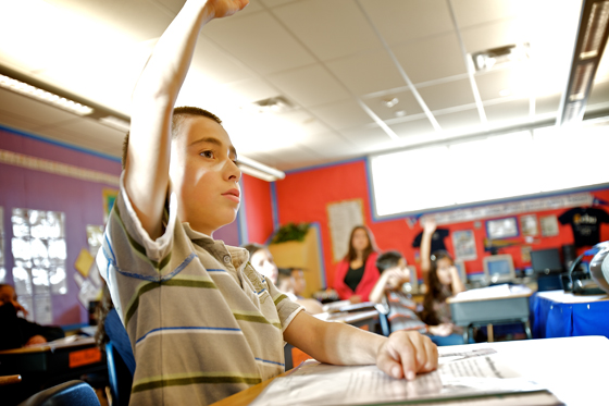 Elementary school student raises hand to ask teacher a question.