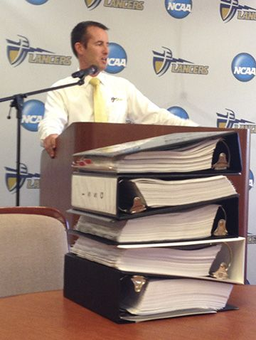 Dr. Micah Parker, CBU athletics director, thanked the CBU community for their efforts as the university worked toward NCAA membership. On the table in front of Parker are the five large notebooks that signify NCAA compliance.