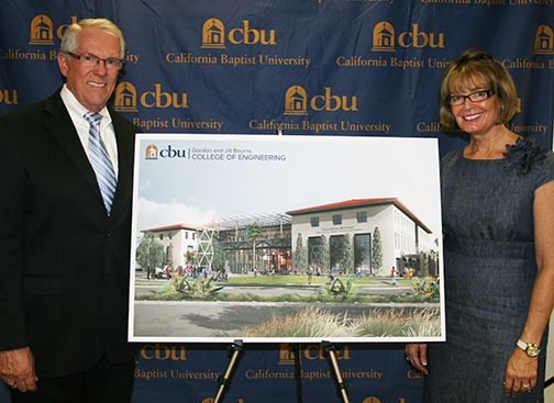 Gordon and Jill Bourns stand next to an architectural drawing for the College of Engineering's new building.