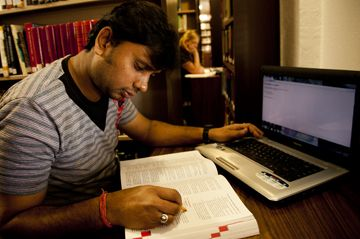 male-student-studying-with-computer-book-in-library-360x239.jpg