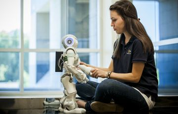 cbu-female-electrical-eng-student-seated-with-robot-360x239.jpg